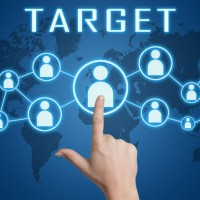 Target concept with hand pressing social icons on blue world map background.
